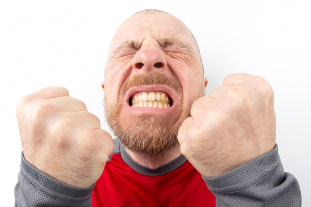 Uomo barbuto con forti emozioni e con il primo piano di pugni chiusi su bianco