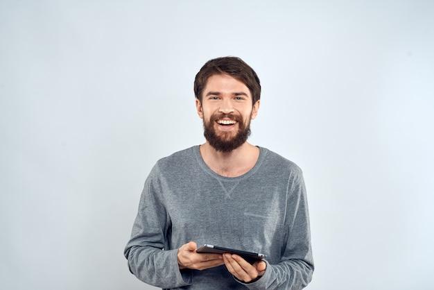 Un uomo barbuto con una tavoletta in mano uno spazio luce internet tecnologia giacca grigia