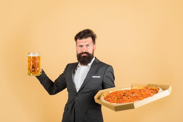 Uomo barbuto con una gustosa pizza e birra in mano pizza time fastfood uomo sorridente con barba tiene