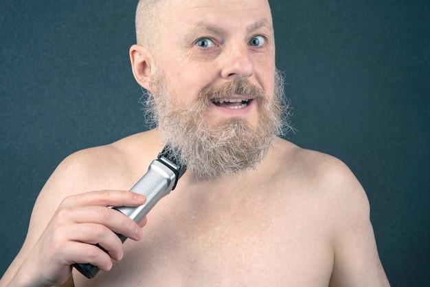 Uomo barbuto con rifinitore per aggiustare la barba in mano. toelettatura e barbiere stile alla moda. correzione della lunghezza della barba