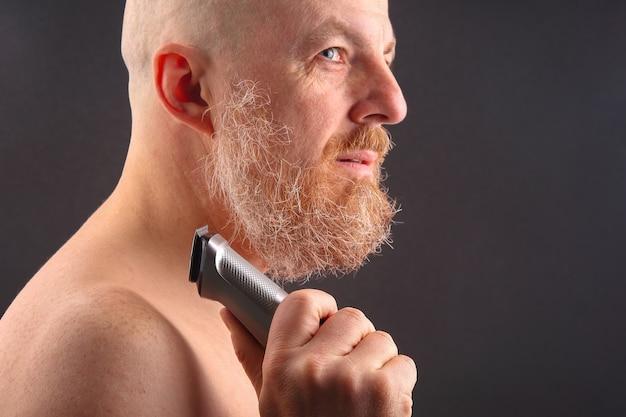 Uomo barbuto con rifinitore per aggiustare la barba in mano