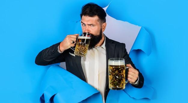 Uomo barbuto con due boccali di birra guardando attraverso il foro della carta. birra bevente maschio alla moda. lager e scuro. oktoberfest.