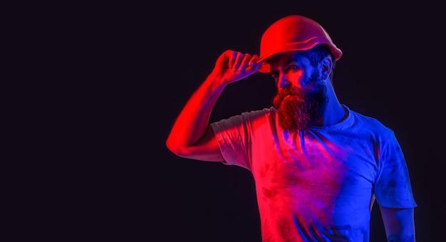 Lavoratore uomo barbuto con la barba nella costruzione di casco o elmetto industria del costruttore dell'uomo