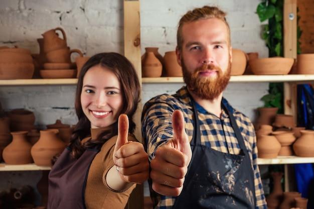 Un uomo barbuto e una giovane donna stanno in piedi e si divertono vicino allo scaffale con vasi e pentole di argilla. vasaio, argilla, vaso, laboratorio di ceramica. maestro e studente