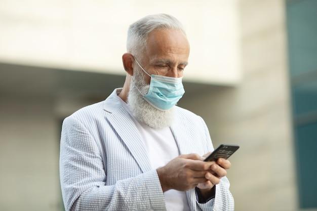 Uomo maturo barbuto con mascherina medica utilizzando il telefono cellulare all'aperto