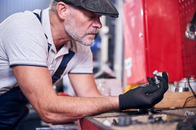 Meccanico barbuto in guanti che tengono bulloni d'argento