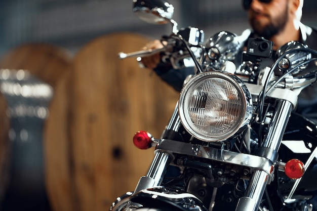 Motociclista barbuto in abiti di pelle nera con la sua moto