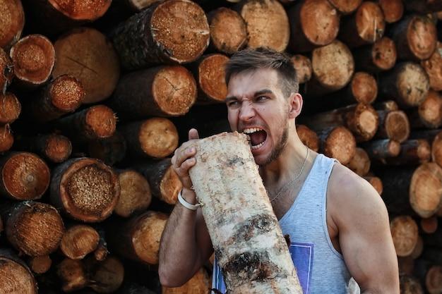 Persona barbuta vicino alla catasta di legname