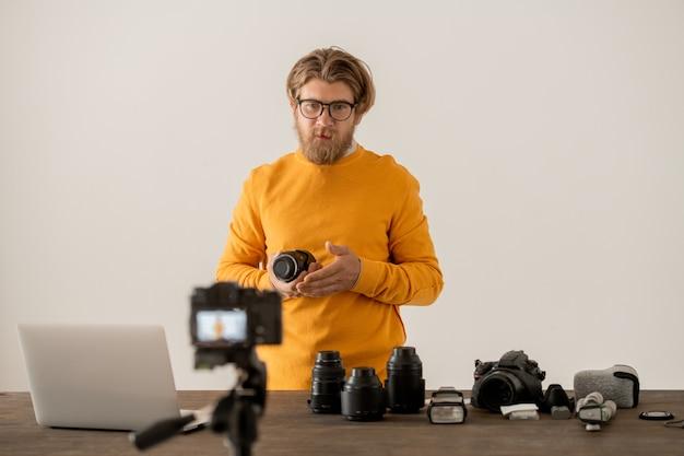 Fotografo barbuto che mostra le parti componenti del nuovo modello di fotocamera professionale al suo pubblico online durante la lezione