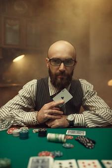 Il giocatore di poker barbuto mostra la carta dell'asso
