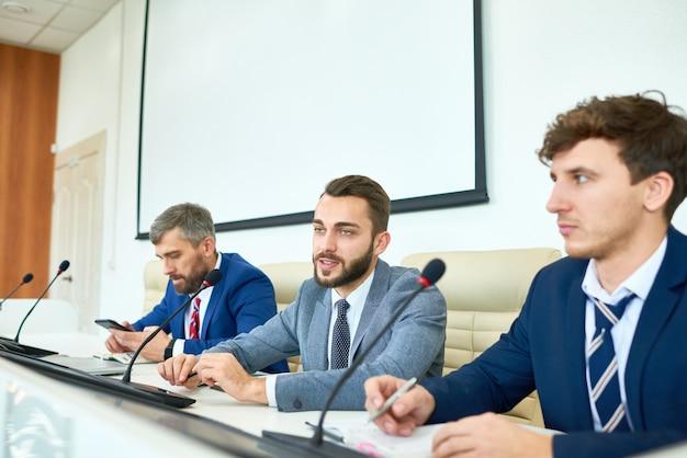 Politico barbuto che parla nella conferenza stampa