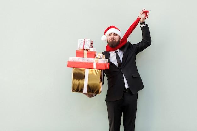 Uomo d'affari barbuto con tristezza che tiene in mano una confezione regalo, compra molti regali e non ha soldi