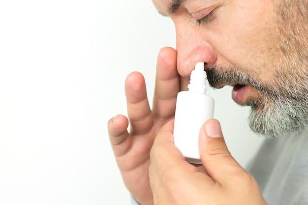 Uomo anziano barbuto che applica spray per naso che cola. trattamento del raffreddore e del concetto di influenza