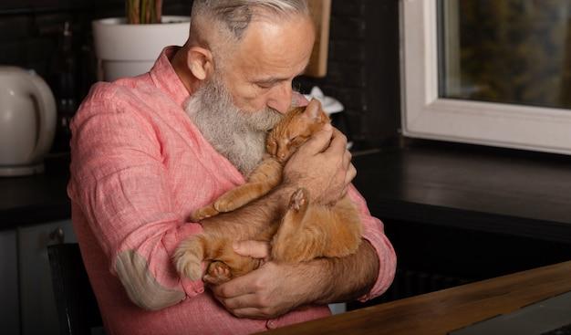 Uomo senior barbuto che tiene gatto sveglio a casa.