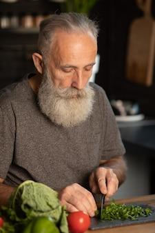 Uomo senior barbuto che prepara insalata sana e saporita in cucina.