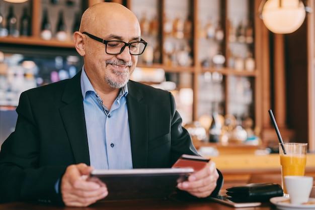 Anziano barbuto in vestito facendo uso della compressa e della carta di credito mentre sedendosi nel self-service.