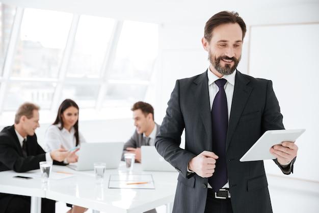 Uomo d'affari sorridente barbuto che guarda il tablet in mano in ufficio con i colleghi