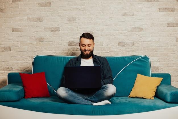 Barbuto uomo sorridente guardando lo schermo del laptop, mentre è seduto sul divano turchese a casa.