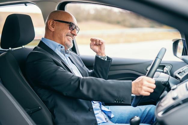 Uomo d'affari adulto senior barbuto sorridente che conduce automobile durante il giorno. mano sul volante