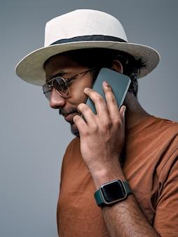 Ragazzo barbuto ed elegante con cappello bianco e orologi parla usando il suo smartphone in uno sfondo grigio.