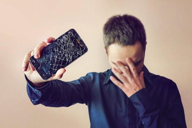 Un uomo barbuto e sconvolto tiene in mano un tablet o uno smartphone fuori uso. su uno sfondo chiaro. schermo rotto