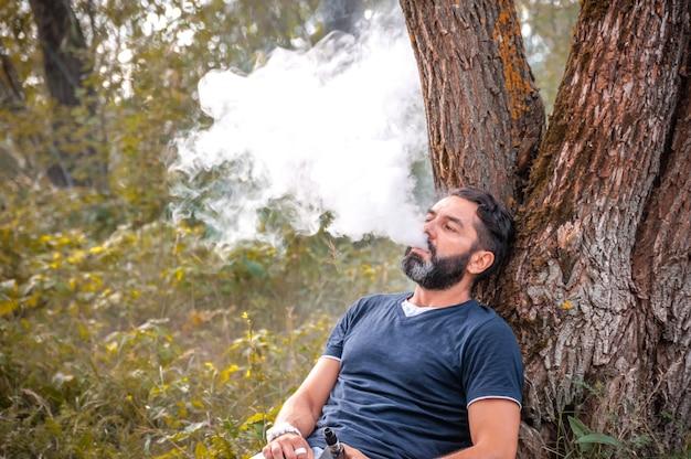 Vaper barbuto che fuma una sigaretta elettronica all'aperto