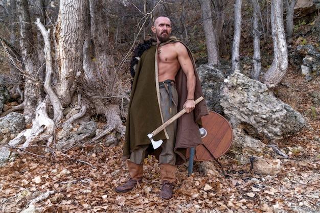 Un vichingo barbuto con una pelle di animale gettata sulle spalle si trova nella foresta e tiene un'ascia tra le mani