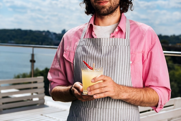 Cameriere barbuto. esperto cameriere barbuto con i capelli lunghi che fornisce un servizio ai suoi clienti mentre porta i cocktail