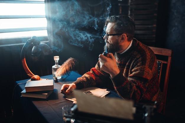 Scrittore barbuto in bicchieri che fuma la pipa