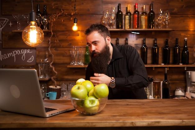 Giovane barista barbuto che si controlla nel computer portatile. bell'uomo.