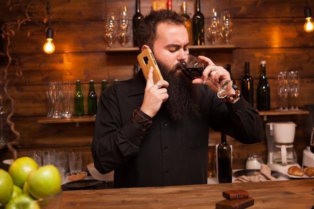 Barbuto giovane batender parlando al telefono prendendosi cura dei suoi affari. pub alla moda.
