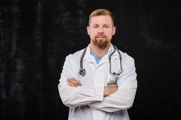 Barbuto giovane medico in whitecoat e fonendoscopio sul collo incrociando le braccia dal petto in isolamento
