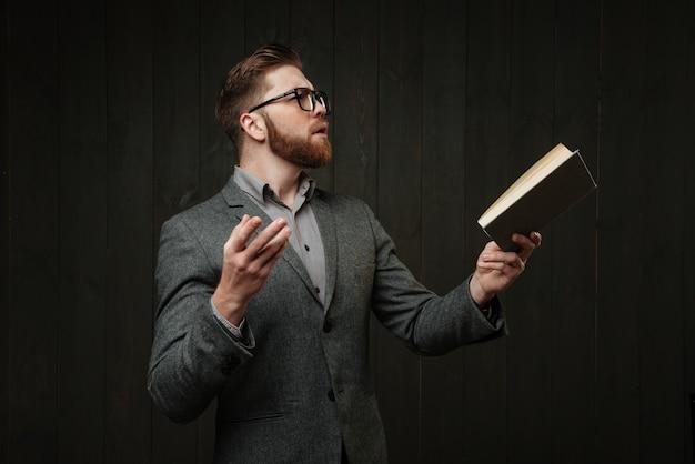 Giovane barbuto in occhiali e vestito casual leggendo un libro e gesticolando con le mani isolate sullo sfondo di legno nero