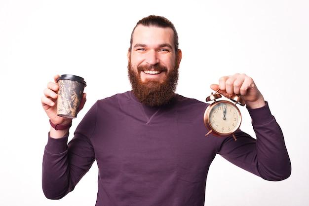Il giovane barbuto sta tenendo un orologio e una tazza di bevanda calda e sorridendo sta guardando la telecamera