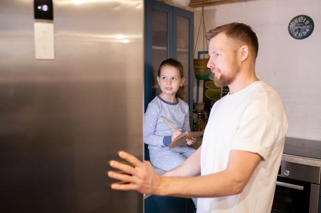 Giovane barbuto che apre la porta del frigorifero mentre la sua piccola figlia sveglia con il blocco note e la matita fa la lista di cosa comprare