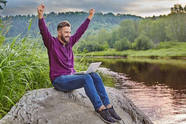 Il giovane barbuto si siede sulla roccia vicino al fiume con il computer portatile in grembo e si rallegra con le mani alzate verso l'alto.