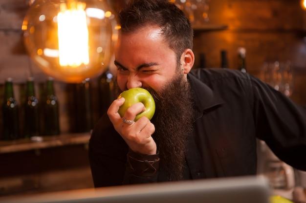 Barista bearderd che mangia una mela verde in un pub vintage