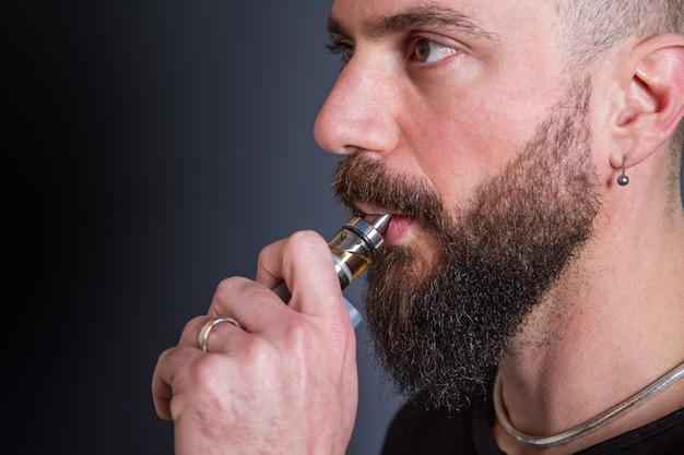 Uomo barbuto che fuma sigaretta elettronica