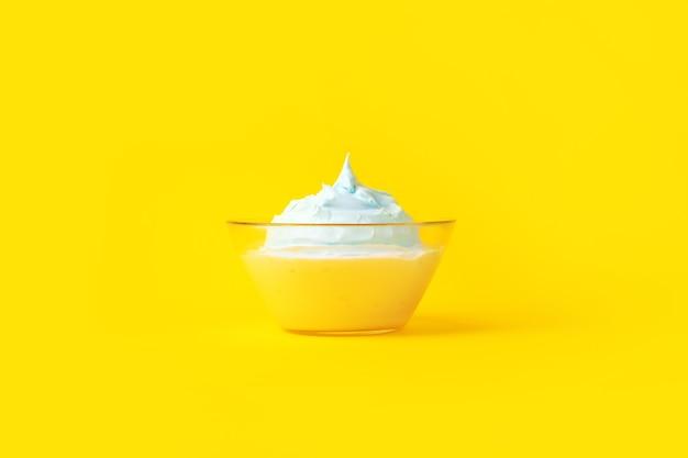 Uova sbattute con lo zucchero in una lastra di vetro, su sfondo giallo, concetto culinario