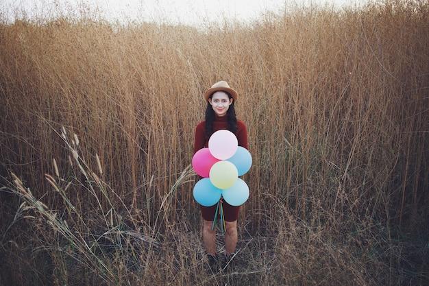 La bella donna asiatica tiene i palloncini e sta in piedi con una bella vista sull'erba limata