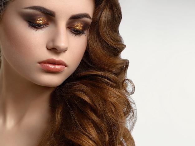 Bellissima modella con capelli ricci marroni che indossa un trucco da sera strepitoso