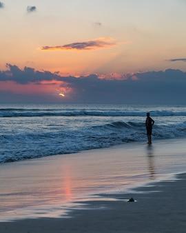 Bei tramonto e siluetta di un uomo sulla spiaggia di seminyak, bali