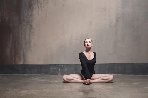 La bella donna si siede nella posa del loto e guarda l'obbiettivo. foto in studio
