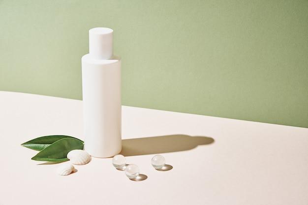 La bottiglia cosmetica del pacchetto del prodotto beaty su sfondo verde pastello cosmetici mock up
