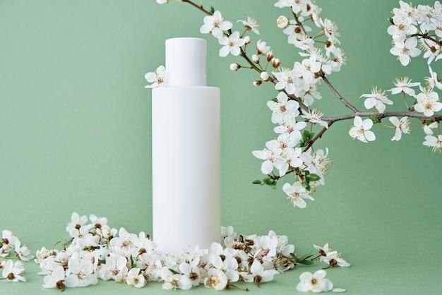 La bottiglia cosmetica del pacchetto del prodotto beaty su sfondo verde pastello con cosmetici di ramo di albero in fiore mock up