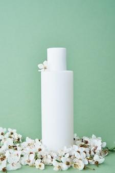 Flacone cosmetico con confezione di prodotti beaty su sfondo verde pastello con cosmetici per rami di albero in fiore mock up