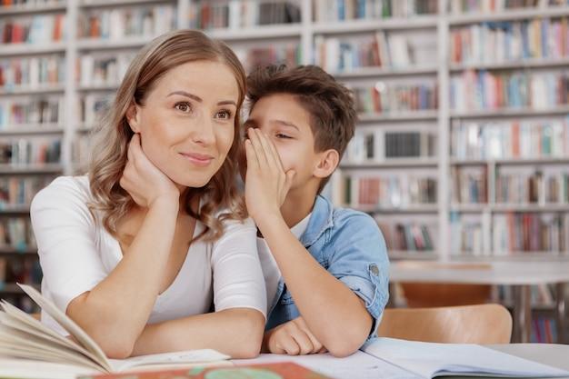 Donna beauitful che sorride quando il suo giovane figlio che bisbiglia al suo orecchio alla biblioteca
