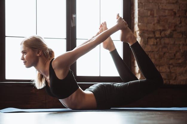 La giovane donna beauitful che allunga e che fa l'yoga si esercita sulla stuoia