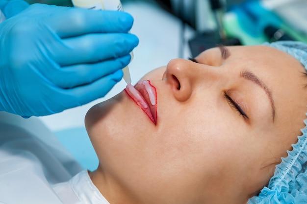 Estetista, anestesia sulle labbra per il trucco permanente delle labbra. tatuaggio labbra