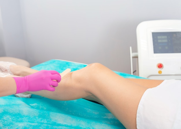 L'estetista applica l'idro gel per trattamenti laser sulla gamba femminile